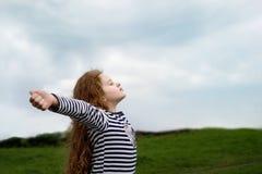 Het meisje sloot haar ogen en ademhaling met verse blazende lucht royalty-vrije stock fotografie