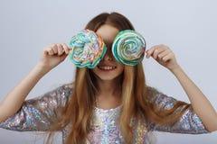Het meisje sloot haar ogen met ronde, multi-colored suikergoedglimlachen Lang blond haar royalty-vrije stock foto's
