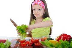 Het meisje sneed salade bij de lijst Stock Afbeeldingen