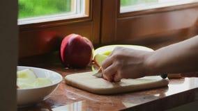 Het meisje snijdt de appelen om een cake te maken stock video