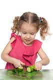 Het meisje snijdt komkommer Royalty-vrije Stock Fotografie