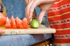 Het meisje snijdt komkommer royalty-vrije stock foto's