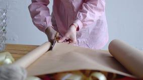 Het meisje snijdt verpakkend kraftpapier-document stock videobeelden