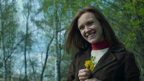 Het meisje snuift de de lente gele bloemen stock videobeelden