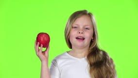 Het meisje snuift en bijt een appel Het groene scherm Langzame Motie stock footage