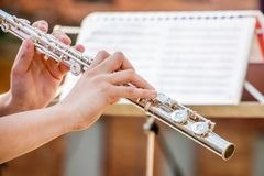 Het meisje speelt de fluit Fluit in de handen van de musicus dur royalty-vrije stock foto