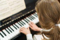 Het meisje speelt de piano stock afbeelding