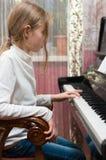 Het meisje speelt de piano stock foto's