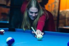Het meisje speelt een biljart bij de club stock foto