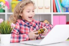 Het meisje speelt een computerspel Stock Foto's