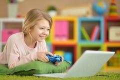 Het meisje speelt een computerspel Stock Fotografie