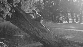 Het meisje speelt in een mooi die de zomerpark, door de zon wordt aangestoken stock videobeelden