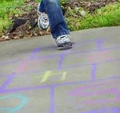 Het meisje speelt Hinkelspels Stock Fotografie