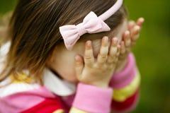 Het meisje speelt huid-en-zoekt verbergend gezicht Stock Fotografie
