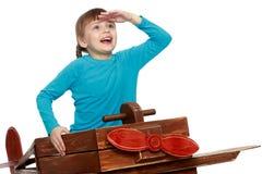 Het meisje speelt met een groot stuk speelgoed vliegtuig stock afbeelding