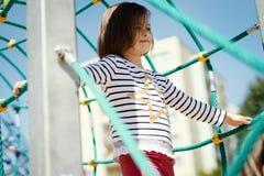 Het meisje speelt op de speelplaats in de zomer Stock Afbeelding