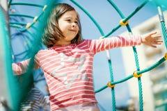 Het meisje speelt op de speelplaats in de zomer Stock Afbeeldingen