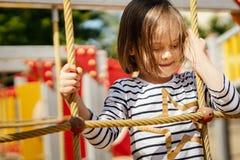 Het meisje speelt op de speelplaats in de zomer Stock Fotografie