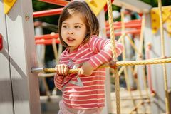 Het meisje speelt op de speelplaats in de zomer Stock Foto