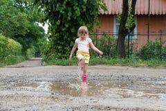 Het meisje speelt in het water in het midden van een geruïneerde weg, na regen royalty-vrije stock fotografie