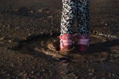 Het meisje speelt in water, natte vuile schoenen, in het midden van vulklei, onvergetelijke ogenblikken, kinderen` s vermaak Conc stock foto's