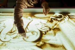 Het meisje in het spel trekt haar vingers op het zand met een backlight stock foto's