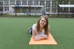 Het meisje in sporten kleedt het liggen op de Mat op het kunstmatige gras op de Speelplaats en kijkt recht, portret van een jonge stock foto's