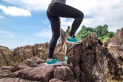 Het meisje in sportkleding op de rotsen Royalty-vrije Stock Afbeeldingen