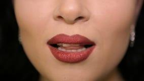 Het meisje spreekt de woorden op de camera De lippen met rode lippenstift stock video