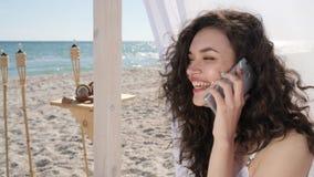 Het meisje spreekt door androïde dichtbijgelegen overzees, wijfje die door mobiel en lach, telefoongesprek voor meisje bij strand stock videobeelden