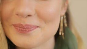 Het meisje spreekt met perziklippenstift op haar lippen stock footage