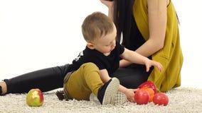 Het meisje spreekt op de telefoon, eet haar kind een appel Witte achtergrond stock videobeelden