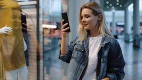 Het meisje spreekt op de telefoon en de films een video die op haar smartphone zich vóór een showvenster bevinden in een winkelco stock footage