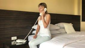 Het meisje spreekt op de telefoon in het hotel stock videobeelden