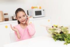 Het meisje spreekt op de telefoon in de keuken Zij zit bij de lijst en spreekt enthousiast stock foto's