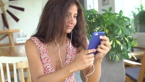 Het meisje spreekt op haar smartphone gebruikend hoofdtelefoons stock videobeelden