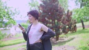 Het meisje spreekt tekst op een smartphone stock footage