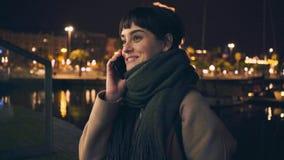 Het meisje spreekt telefonisch bij nacht stock videobeelden