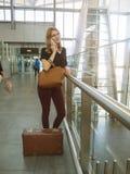 Het meisje spreekt telefonisch en wacht op de vlucht in de luchthaven Stock Fotografie