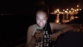 Het meisje spreekt telefonisch met hoofdtelefoons bij nacht stock videobeelden