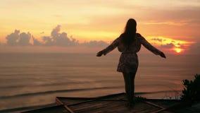 Het meisje spreidt wapens wijd open bij strand uit bekijkt zonsondergang en oceaan, langzame motie stock video