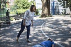Het meisje staat een onbewuste kerel na ongeval bij Royalty-vrije Stock Fotografie