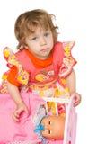 Het meisje stapelt een naakte pop Stock Afbeeldingen