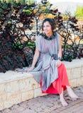 Het meisje steeg haar schoenen op om haar benen te rusten en zat op de rand stock fotografie