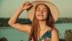 Het meisje stijgt haar hoed op de achtergrond van een mooie rivier en een groene bos Langzame motie op stock footage