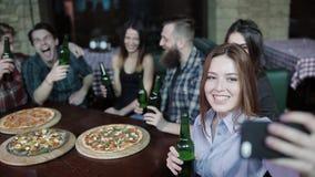Het meisje stijgt op de telefoon een vrolijk bedrijf van vrienden in een bierhuis op stock videobeelden