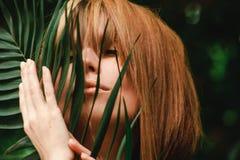 Het meisje streelt zacht een varentak over haar gezicht stock foto