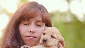 Het meisje strijkt een klein puppy stock video