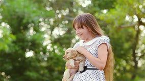 Het meisje strijkt een puppy op handen stock video