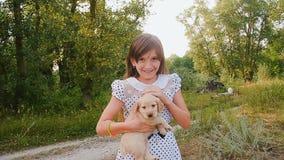 Het meisje strijkt een puppy op handen stock videobeelden